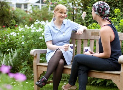 A nurse talks to a female patient wearing a headscarf in the garden at The Christie.