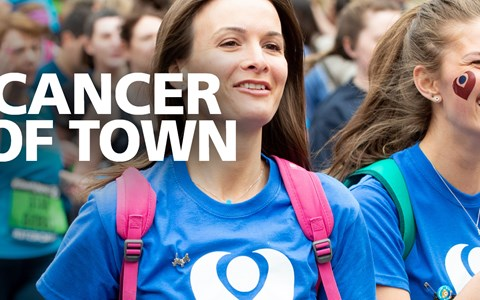Two female fundraisers running the Great Manchester Run for The Christie, the tagline is Run Cancer Out Of Town.
